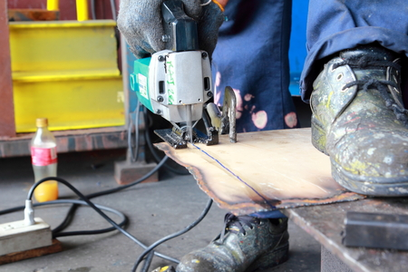 flooring cork: The process of cutting sheet metal with a jigsaw. Stock Photo