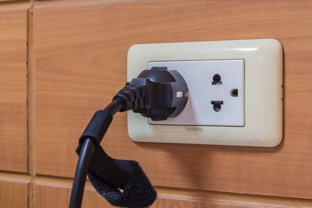 power cord: Electrical outlet with black power cord. Stock Photo
