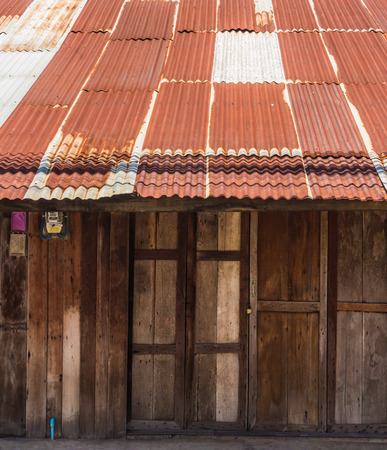 house with style: Wooden house tin roof ,Old Thai style wooden house with rusty zinc roof
