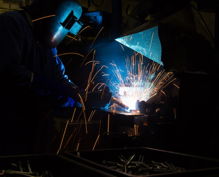 fabricator: Welder uses torch to make sparks during manufacture of metal equipment.