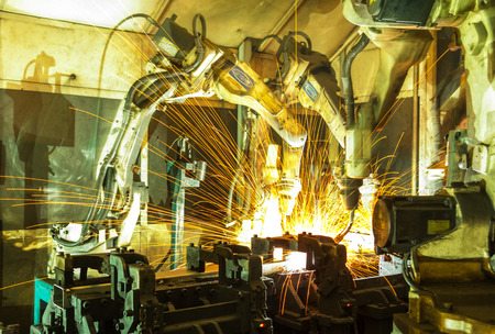 welding machine: Team welding robots represent the movement. In the automotive parts industry. Stock Photo