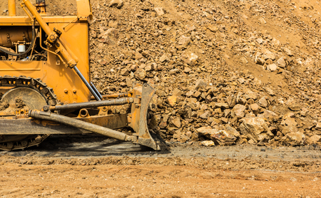 sand quarry: industrial bulldozer moving earth and sand in sand pit or quarry