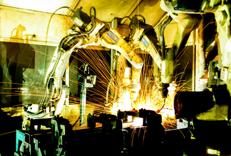 Team welding robots represent the movement. In the automotive parts industry. Foto de archivo