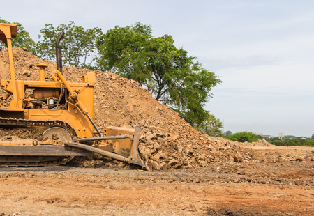 earth moving: industrial bulldozer moving earth and sand in sand pit or quarry
