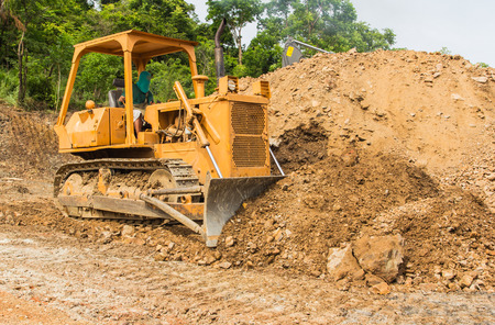sand quarry: industrial backhoe, bulldozer moving earth and sand in sandpit or quarry
