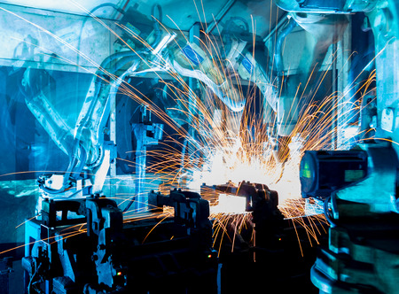 Team welding robots represent the movement. In the automotive parts industry. Stock Photo
