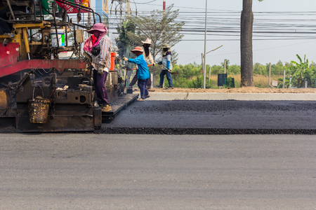 budget repair: machine and worker at road construction Stock Photo