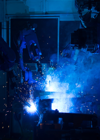 mechanical parts: Team welding robots represent the movement. In the automotive parts industry. Stock Photo