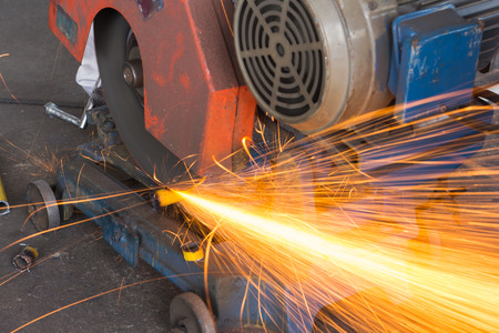 cutoff blade: factory worker using electric grinder Stock Photo