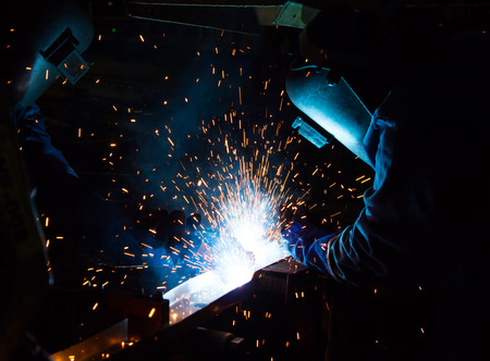 MIG welder uses torch to make sparks during manufacture of metal equipment. Foto de archivo