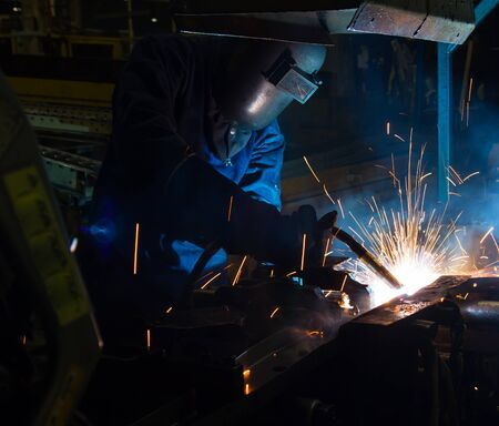 mig: MIG welder uses torch to make sparks during manufacture of metal equipment. Stock Photo