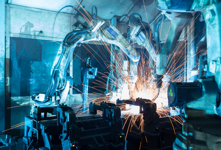 production plant: Team welding robots represent the movement. In the automotive parts industry. Stock Photo