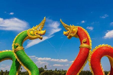 thai temple: The Big Naga snake guarding Thai temple with white cloud and blue sky background Stock Photo