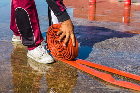 rolling up: The Man rolling up a fire hose after filled  Water