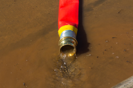 rolling up: rolling up a fire hose after filled  Water Stock Photo