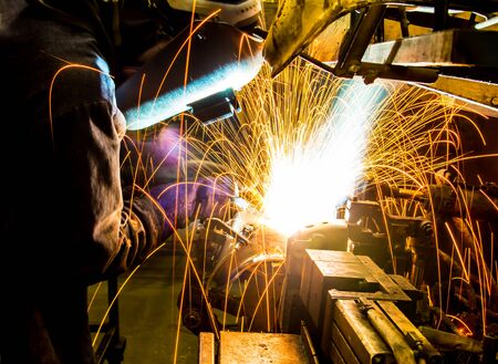 skilled labour: work is welding skills up. Manufacturing of car. Stock Photo