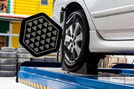 computerized: Car wheel fixed with computerized wheel alignment machine clamp