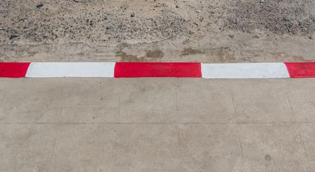 road marking: driveway, sidewalk   Red and white road marking