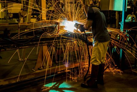 welding mask: MIG welder uses torch to make sparks during manufacture of metal equipment. Stock Photo