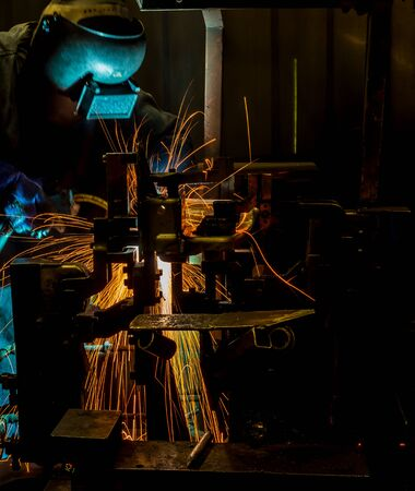 prefabricate: MIG welder uses torch to make sparks during manufacture of metal equipment. Stock Photo