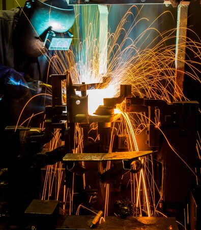 improvisation: MIG welder uses torch to make sparks during manufacture of metal equipment. Stock Photo