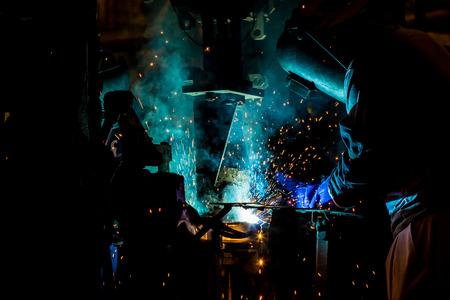 Welder is welding automotive part in factory