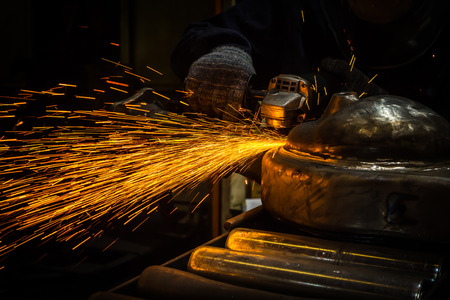 Industry worker cutting metal with grinder Stock Photo