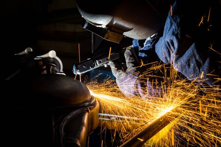 Workers are grooving with carbon welding wires With sparks