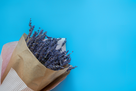 A bouquet of dry lavender in kraft paper on a blue background, symbolizing summer and France. Flat lay, top view.