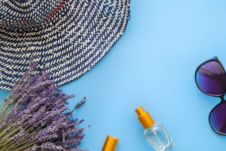 A bouquet of dry lavender in kraft paper on a blue background with a bottle of perfume, sunglasses and a hat, symbolizing summer and France. Flat lay, top view