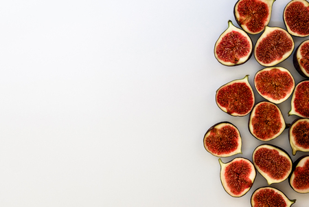 Pattern of sliced ripe figs isolated on white background. Fruit illustration. Food photo. Flat lay, Top view. Copyspace.