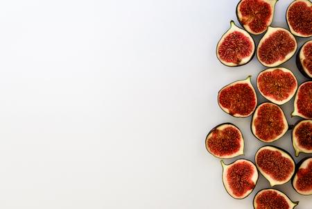 Wzór pokrojone dojrzałe figi na białym tle. Ilustracja owoców. Zdjęcie jedzenia. Leżał na płasko, widok z góry. Copyspace.