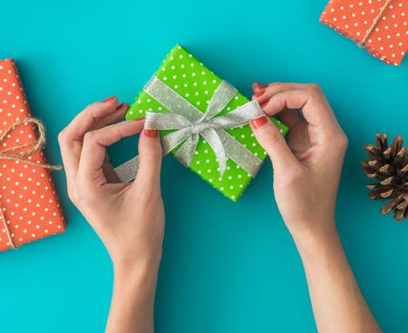 Kerstmis en Nieuwjaar vakantie samenstelling met geschenkdozen, dennenappel, womens handen pack een geschenk op de blauwe achtergrond. Bovenaanzicht, plat leggen. Copyspace. Stockfoto - 90026707