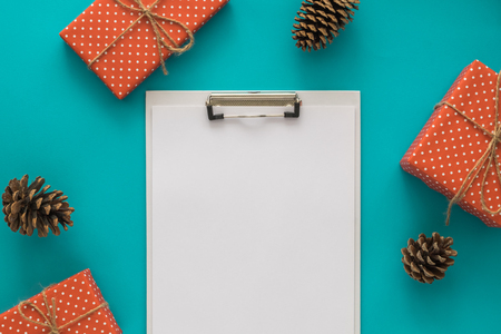todo list: Christmas and New Year holiday to do list with notepad, gift boxes, pine cone on the blue background. Mock up. Flat lay, top view. Stock Photo