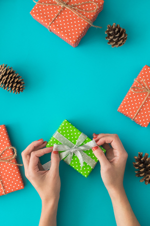 Christmas holiday composition with gift boxes, pine cone, womens hands pack a gift on the blue background. Top view, flat lay. Copyspace. Banco de Imagens - 89917997