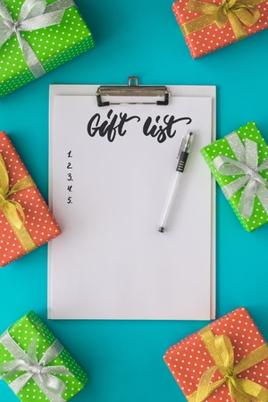 todo list: Christmas and New Year holiday to do list with notepad, pen, gift boxes on the blue background. Mock up. Flat lay, top view. Stock Photo
