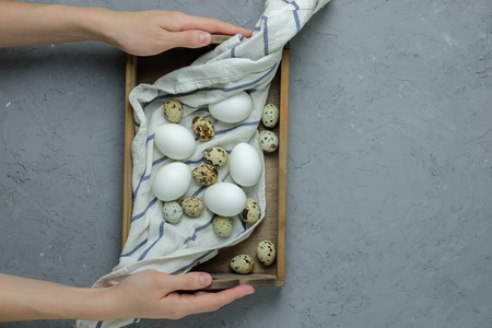 Female Hands Hold Chicken And Quail Eggs In A Wooden Box With A Towel On A