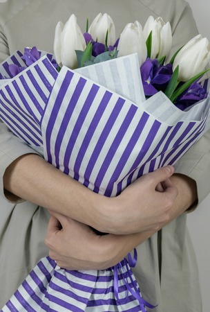 Unrecognizible woman in beige dress holding bouquet of white tulips and violet iris in striped lilac wrapping paper.