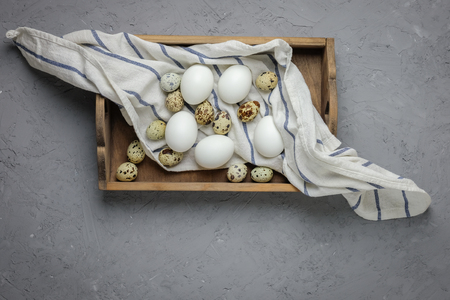 Chicken and quail eggs in a wooden box with a towel on a gray concrete background. Top view. Flat lay. Easter greeting card.