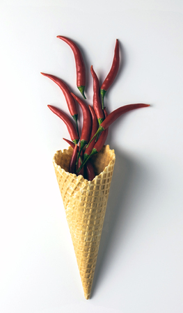 Ice cream waffle cone with red hot little chili peppers isolated on the white background. Foto de archivo