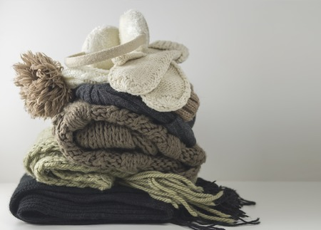 Warm woolen knitted winter and autumn clothes, folded in a pile on a white table. Sweaters, scarves, gloves, hat, headphones. Place for text. Copyspace. Stock Photo