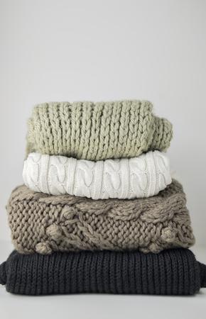 Vêtements d'hiver et d'automne en laine chaude, pliés en tas sur une table blanche. Pulls, écharpes. Place pour le texte. Copyspace.