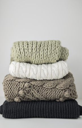 Warm woolen knitted winter and autumn clothes, folded in a pile on a white table. Sweaters, scarves. Place for text. Copyspace.