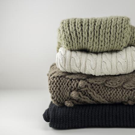Vêtements d'hiver et d'automne en laine chaude, pliés en tas sur une table blanche. Pulls, écharpes. Place pour le texte. Copyspace. Banque d'images