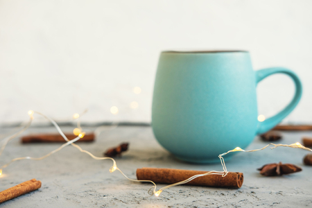 Blue cup of coffee on gray concrete background. Cinnamon sticks, anise stars and garland. Cozy drink autumn and winter concept.