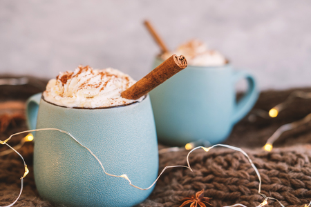 Mug of coffee, cocoa or hot chocolate with whipped cream and cinnamon on scarf with leaves, garland, anise star. Pumpkin latte - cozy drink for cold autumn or winter.