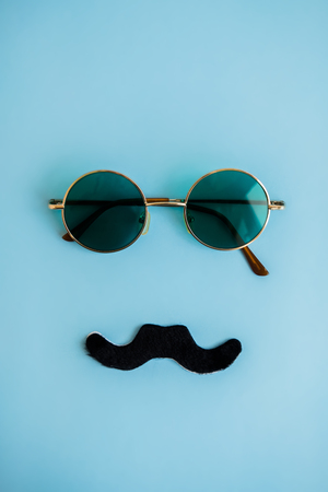 Round green glasses and black mustache on blue background. The concept of man's father's day, month of prostate cancer. Flat lay. Top view Stock Photo