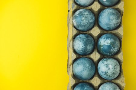 Hand painted blue Easter eggs in wreath on bright yellow