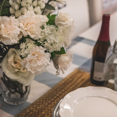 Close-up table setting. On the table are plates on napkin, bottle of wine and vase of flowers