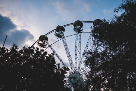Silhouette of a ferris wheel and trees against the sunset sky.